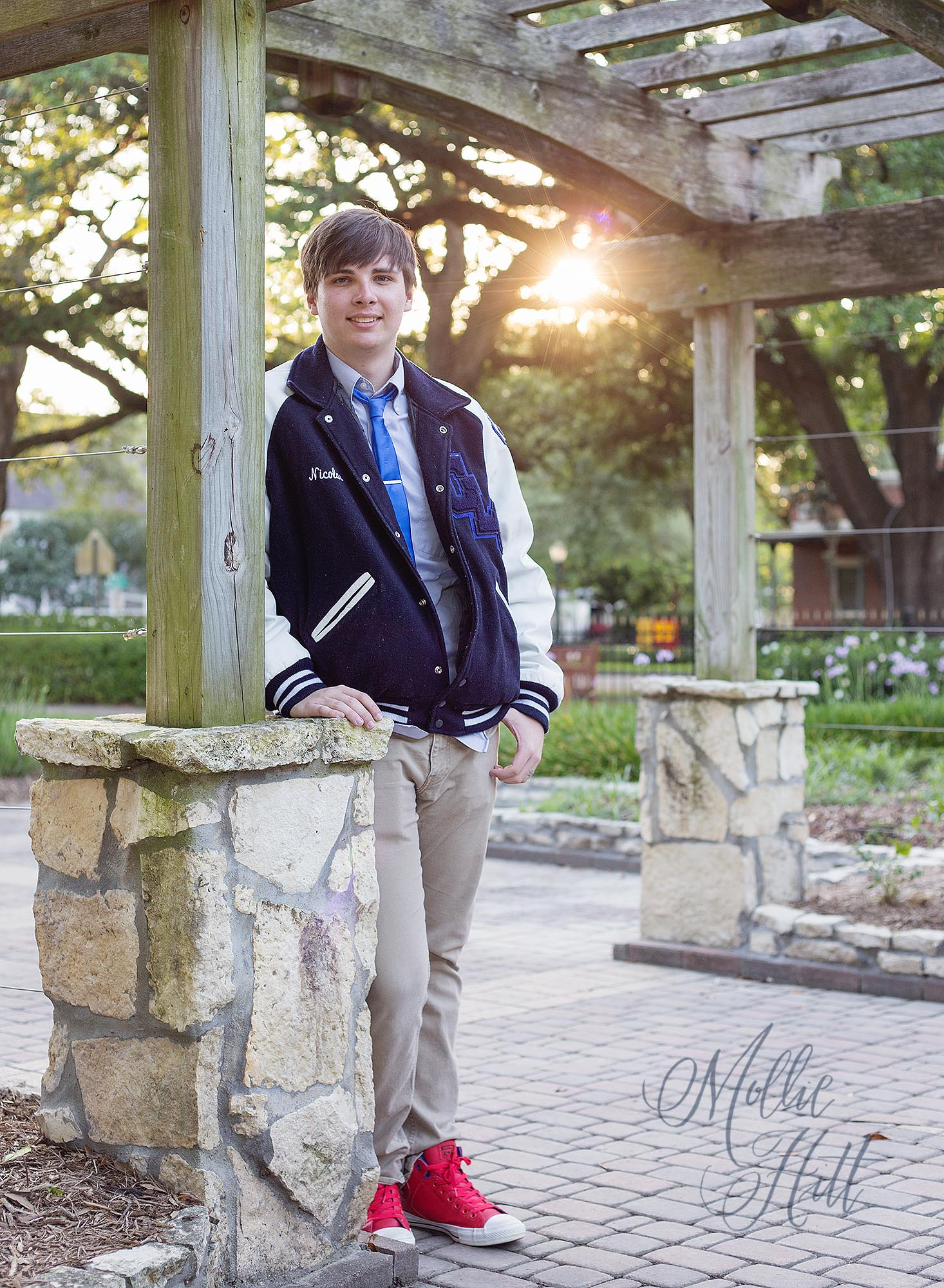Graduating senior boy wearing letterman jacket, leaning against an archway with sunflare in the background