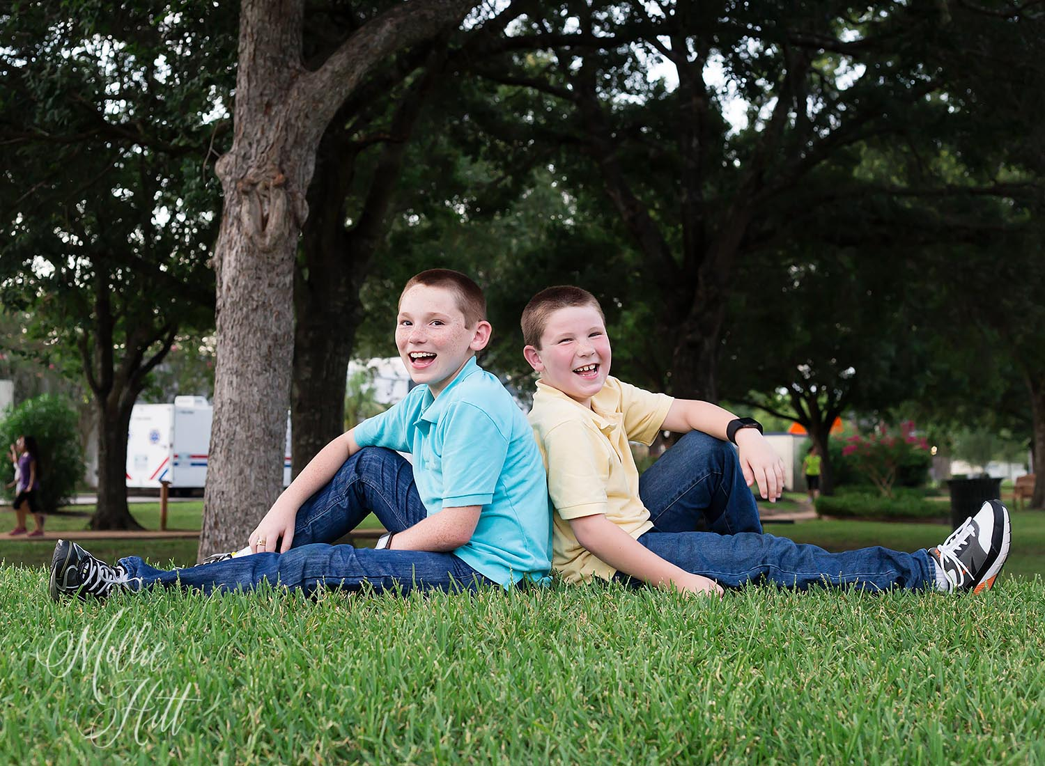Two brothers laugh together on a grassy hill