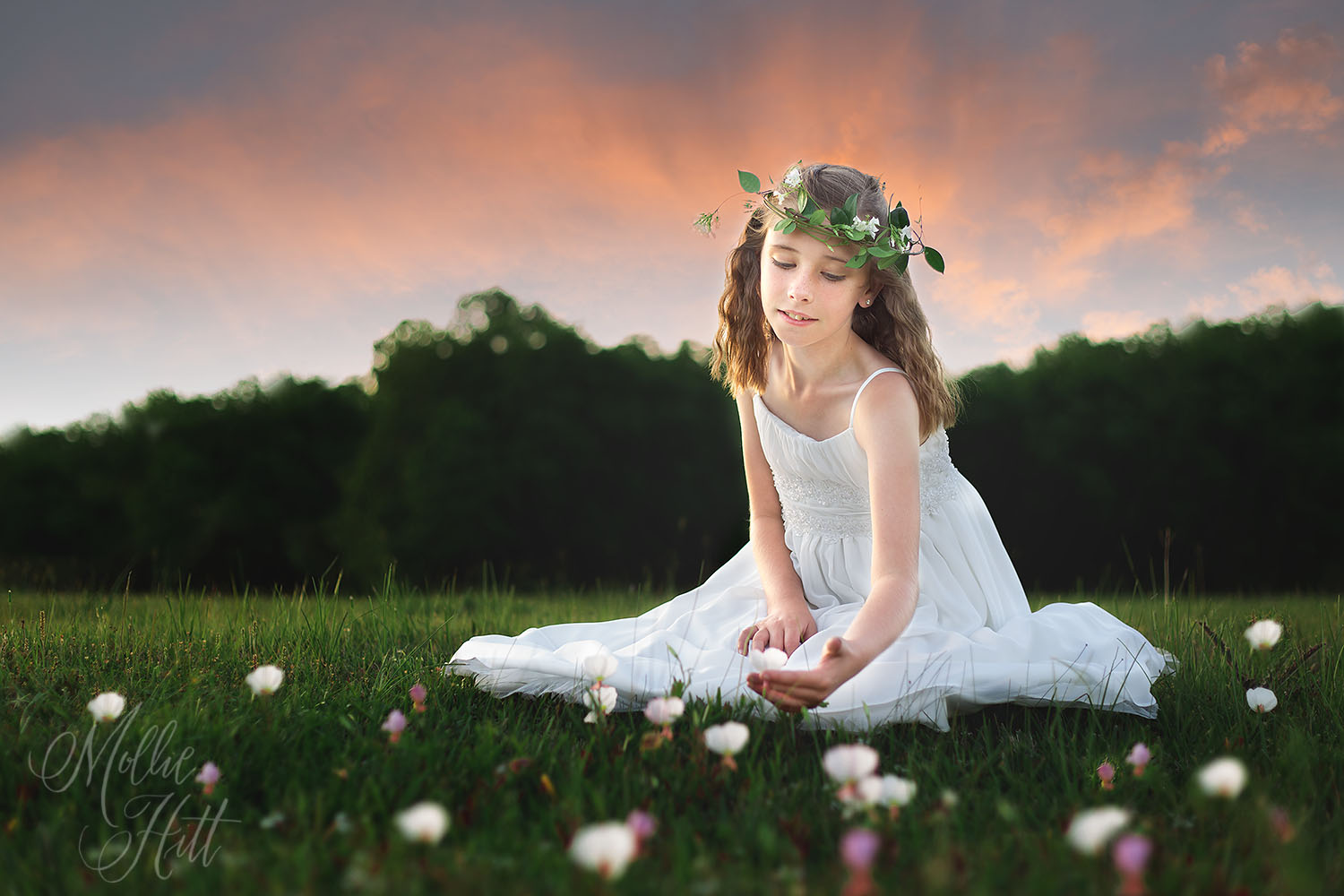 Fairy princess at sunset in a flower field with white floral crown and gown