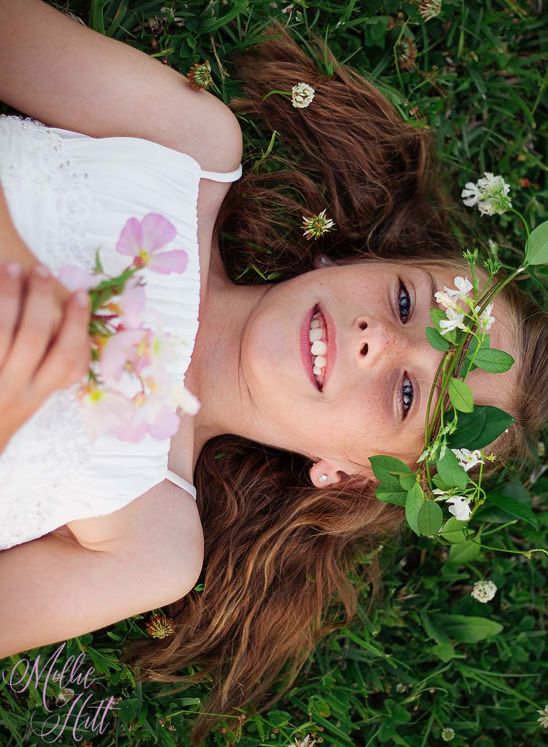 Girl laying on the ground with floral crown and white dress