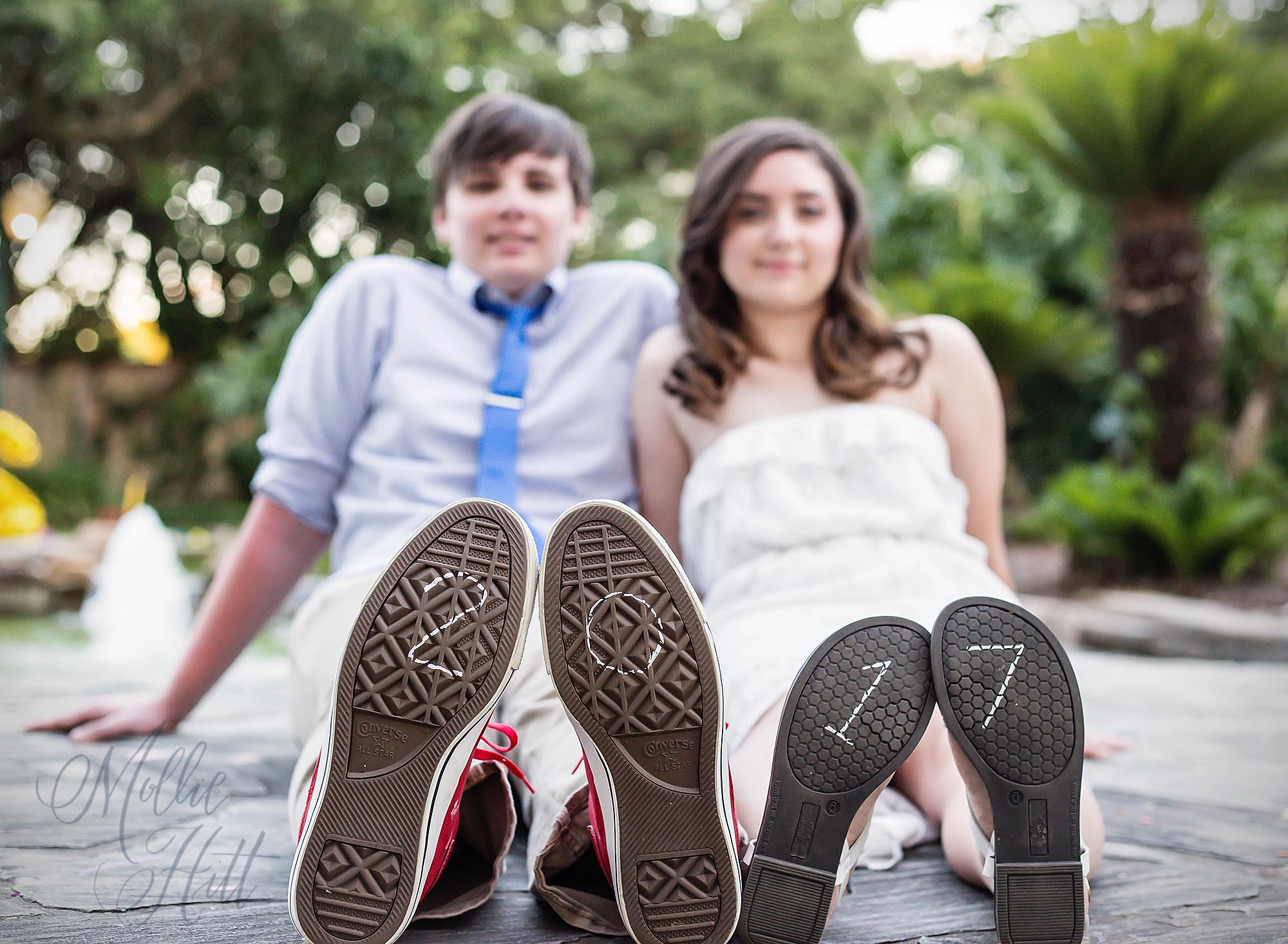 Boyfriend and girlfriend seniors with the year 2017 written on the soles of their shoes