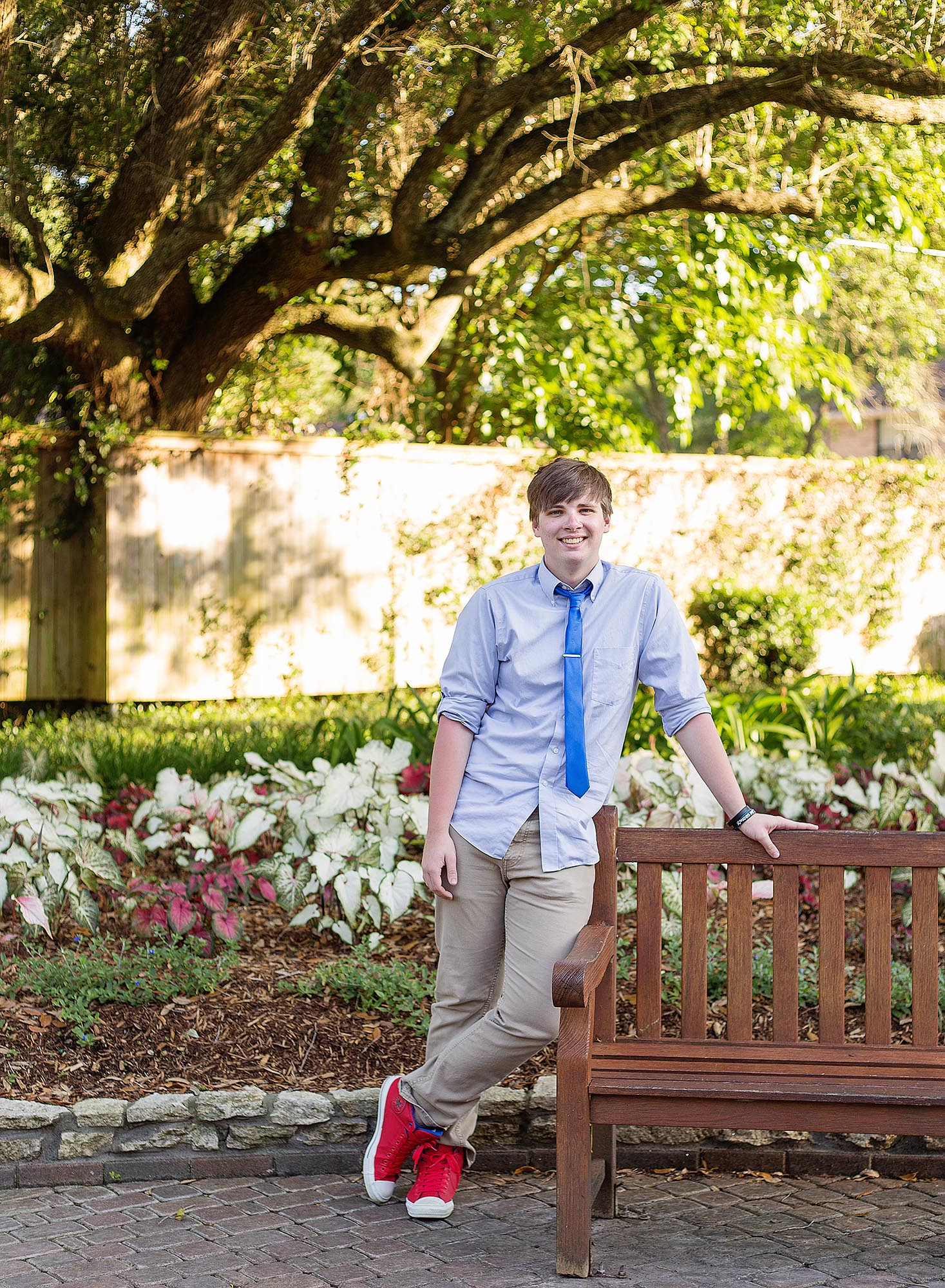 Senior boy with red converse and blue shirt and tie casually leaning against a garden bench and smiling