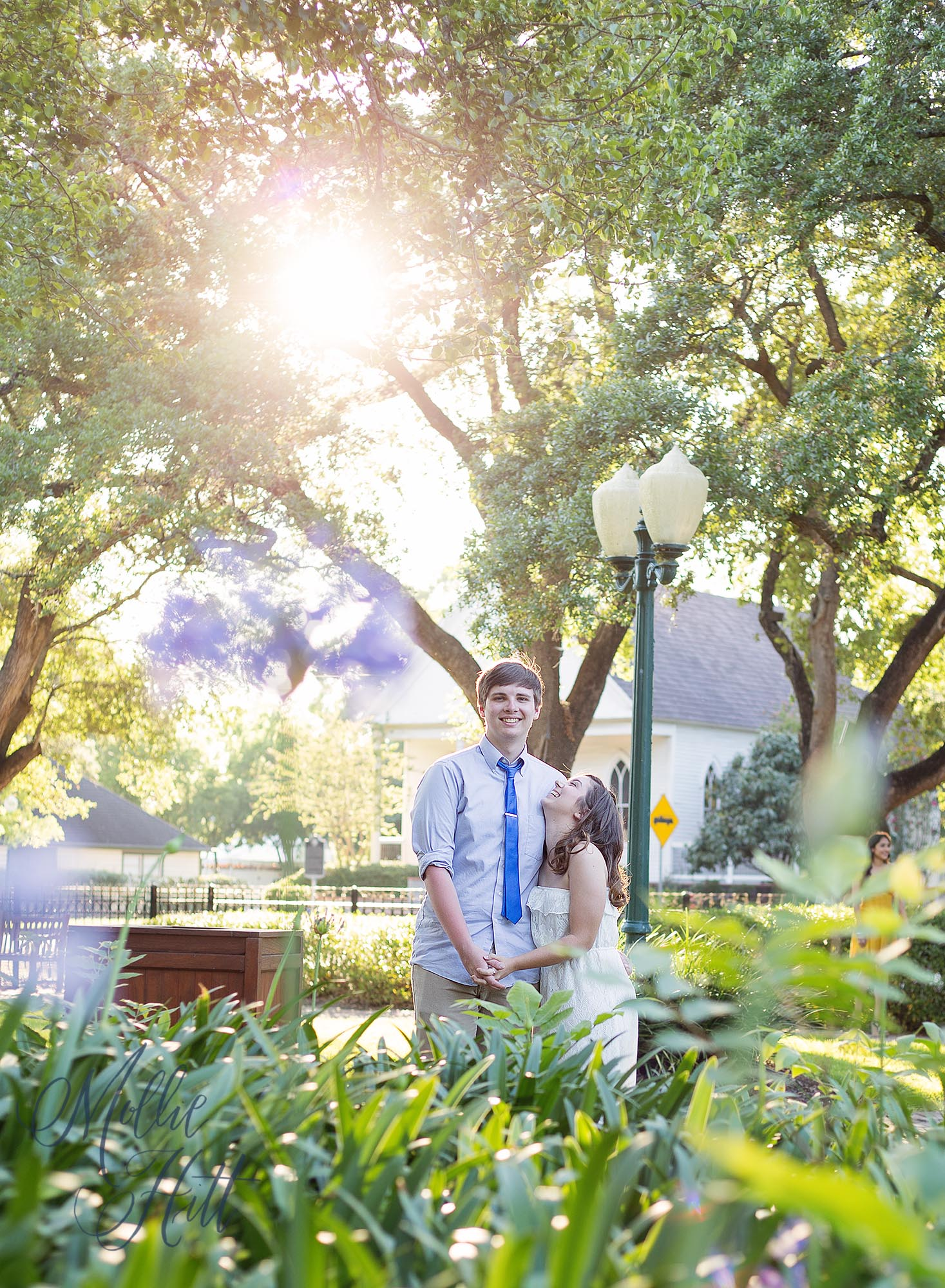 Graduating senior boy and girl couple sharing a romantic moment surrounded by flowers with a warm sun flare at golden hour