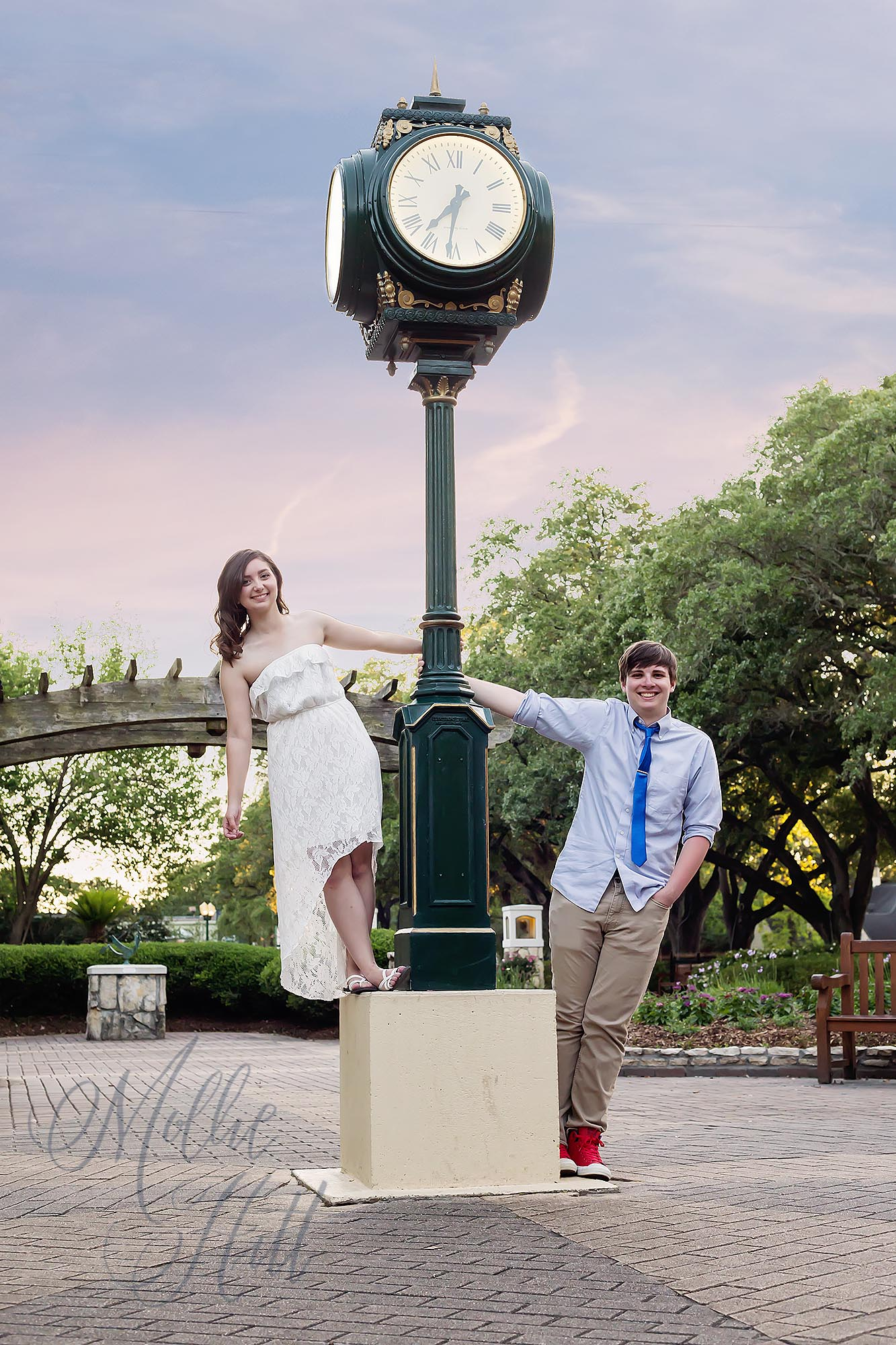 Senior couple posing leaning off of a clock tower in Helen's Garden