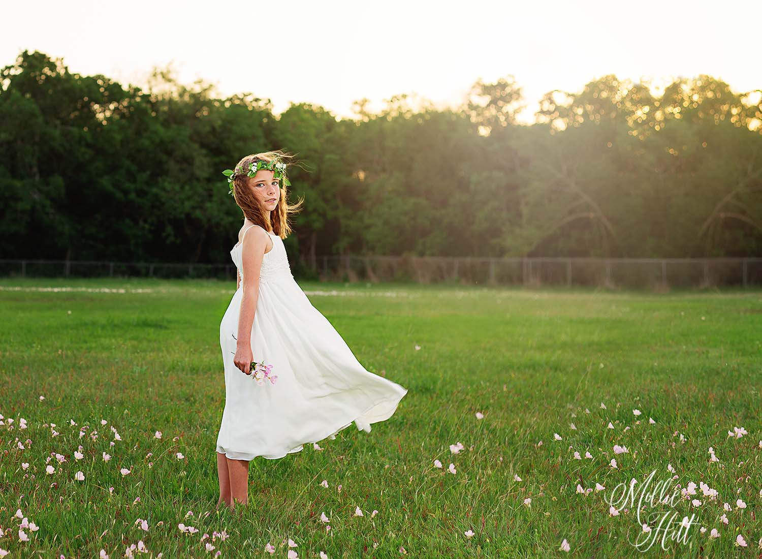 Girl with floral crown in a windblown white dress