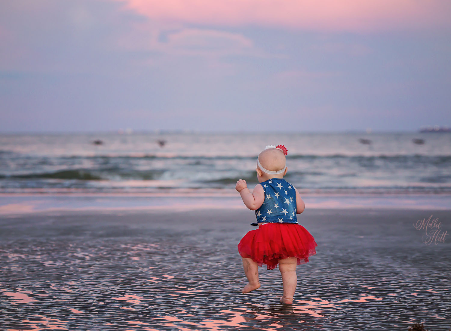 Toddler runs through the wet sand at the beach with a sunset reflecting on the water