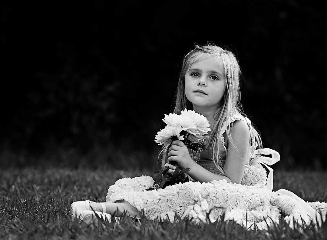Timeless black and white portrait of a young girl sitting in a field