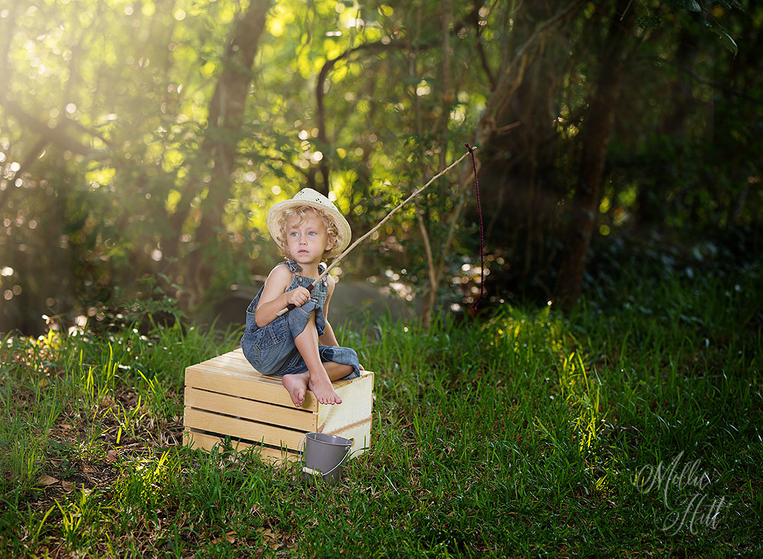 Sunlight streaming in as preschooler in overalls plays in the woods