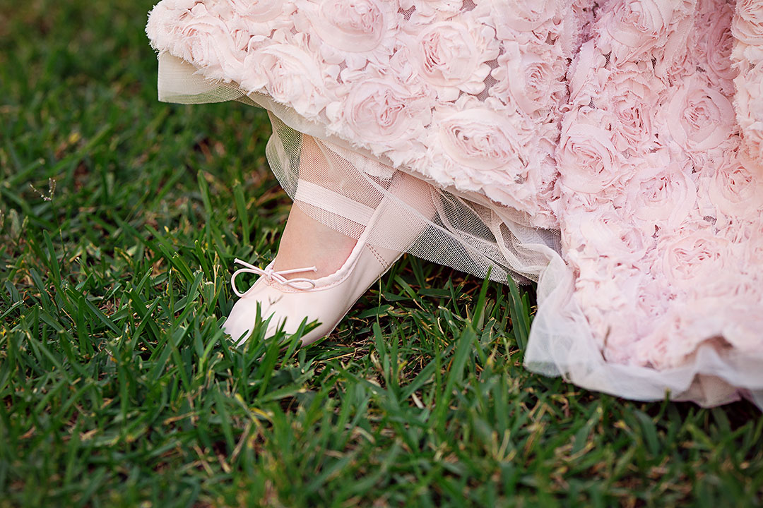 Girl wearing pink ballet shoe steps onto the grass