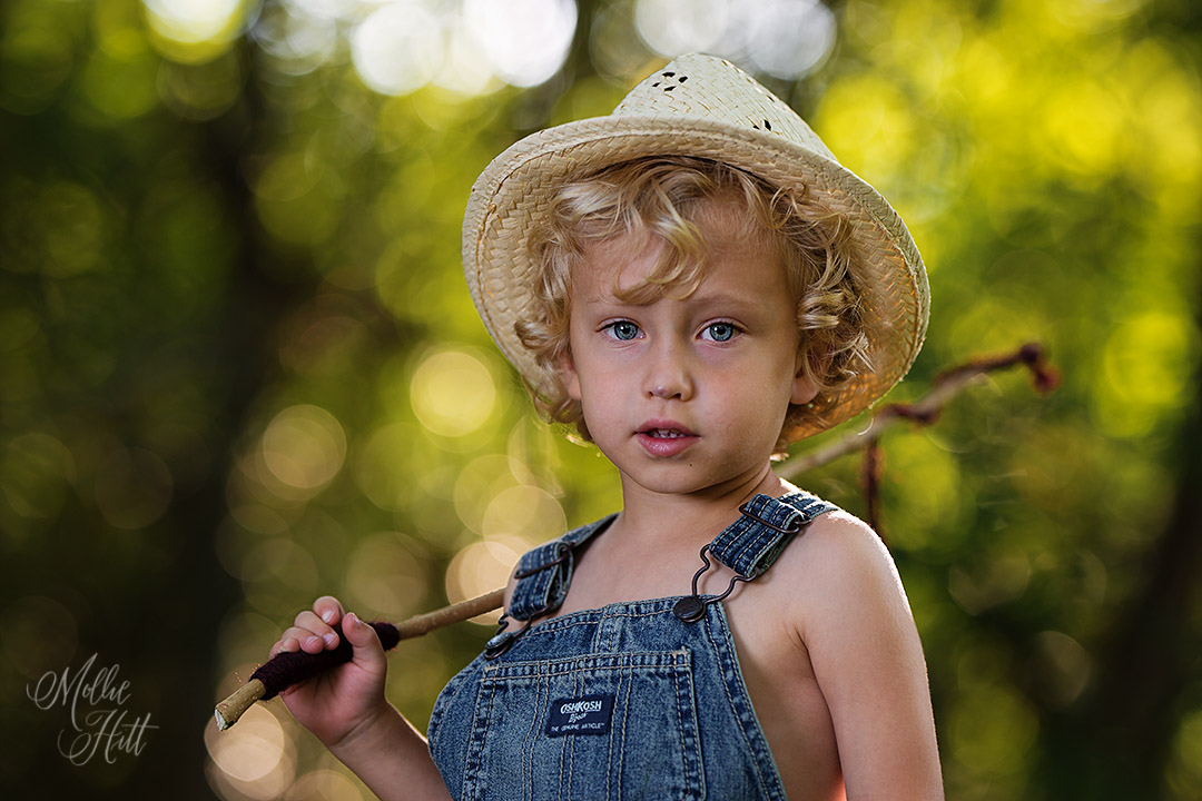 Sweet portrait of blue eyed blond curly haired boy dressed as a fisherman