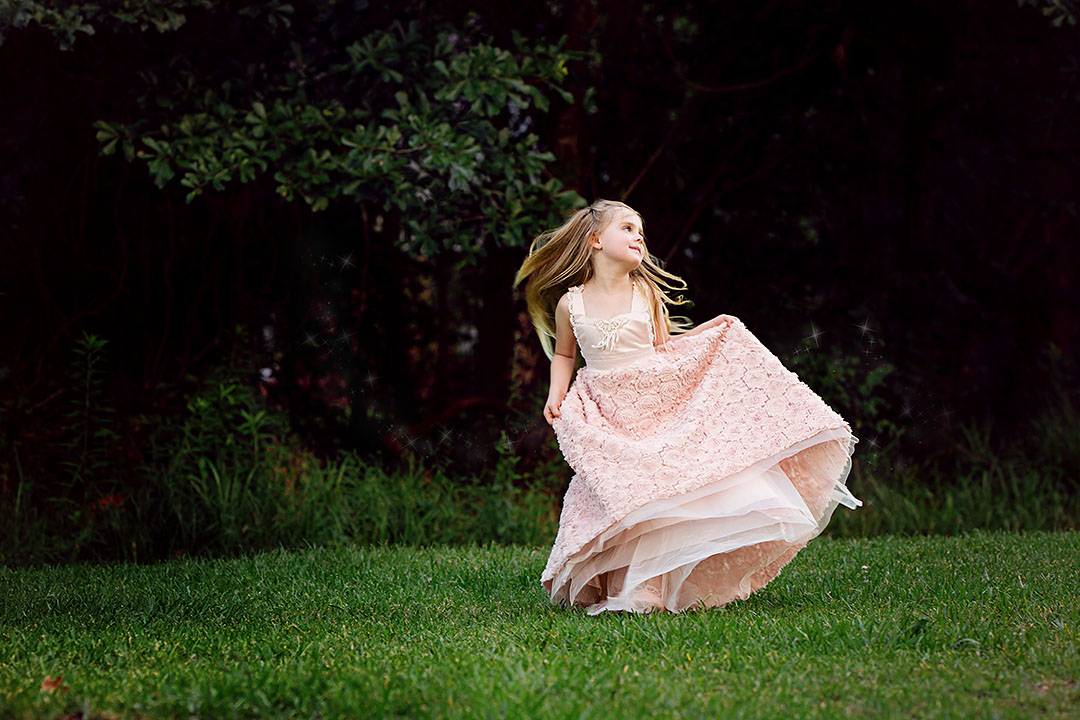 Girl dancing in an open field with beautiful rose gown