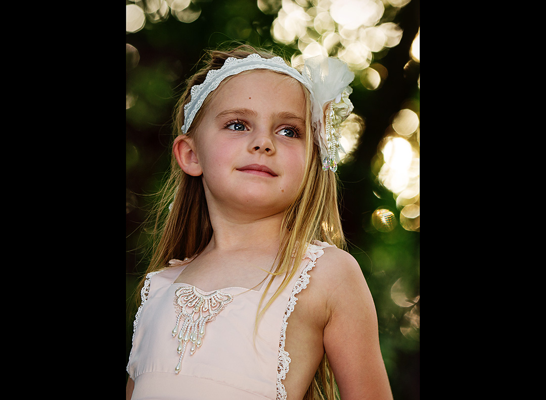 Sweet headshot portrait of a little girl wearing a lacy flower headband with pearls