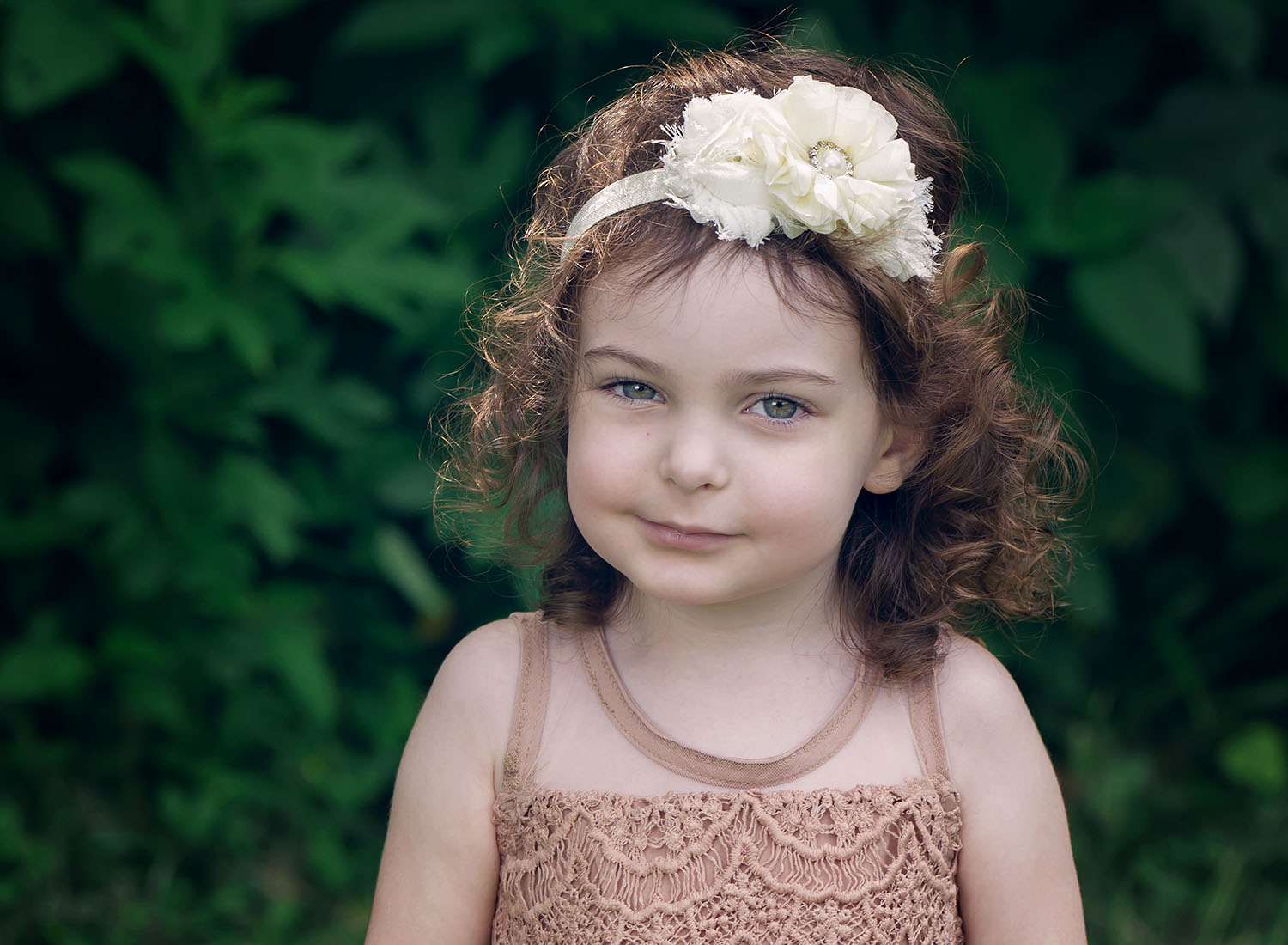 Headshot portrait of curly haired girl in blush lace dress with flower headband