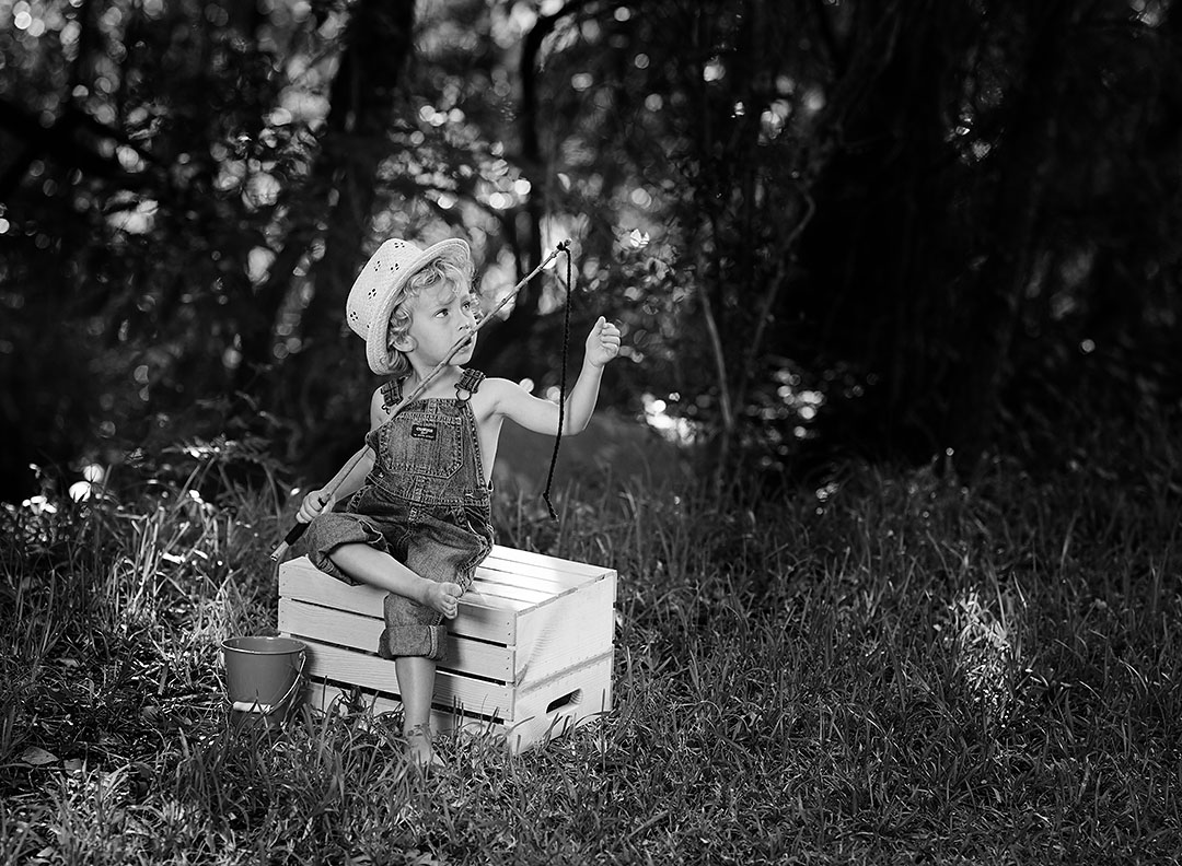 Black and white portrait of preschooler boy with overalls and straw hat