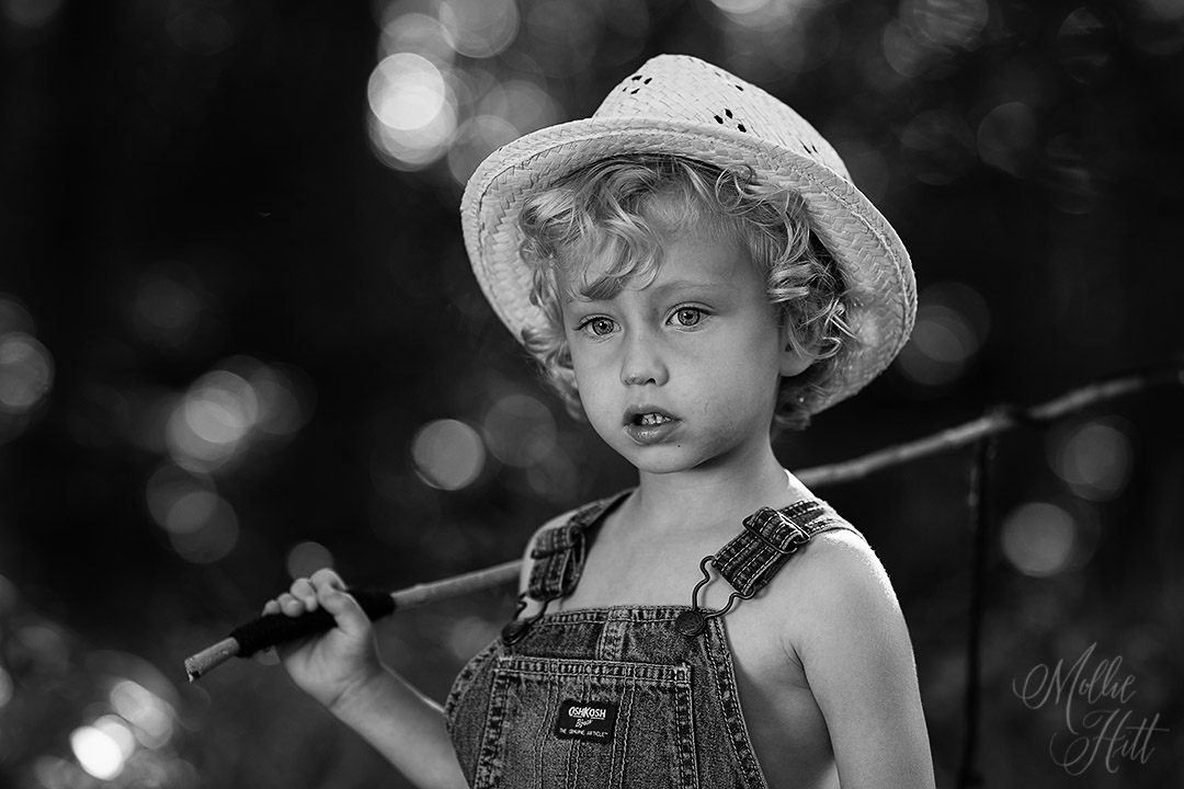 Pensive black and white portrait of toddler wearing overalls and straw hat