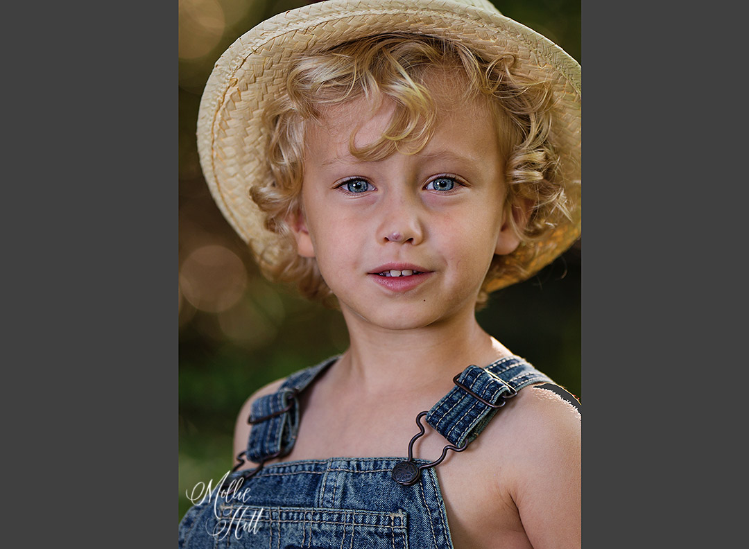 Headshot of little boy with stunning blue eyes and curly blonde hair wearing a straw hat and overalls