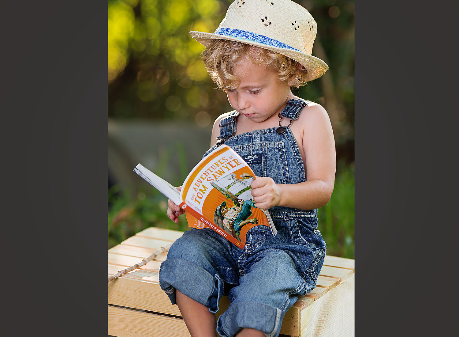 Preschooler reading the adventures of tom sawyer on location