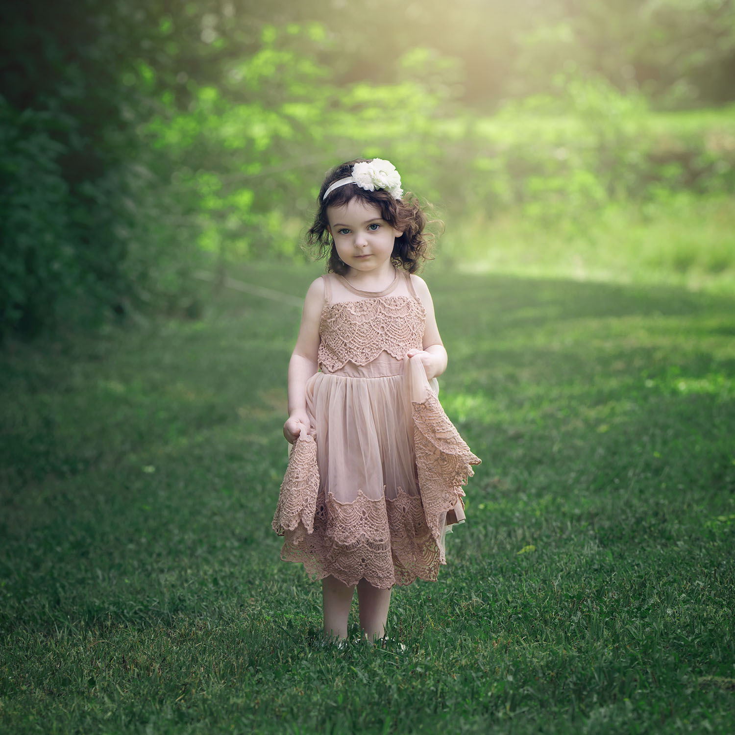 Little girl with brown hair in beautiful blush lacy dress in the woods
